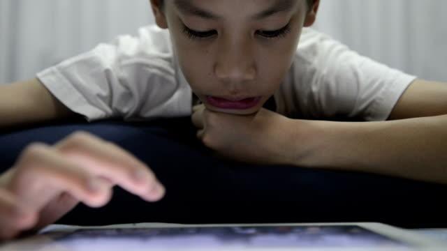Boy playing digital tablet