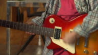 CU,  PAN,  Boy (8-9) playing electric guitar