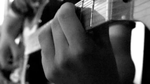 Boy playing guitar close up