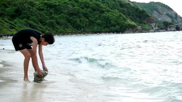 Junge, spielen am Strand mit Steinen