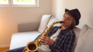 MS Boy playing saxophone on living room couch