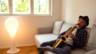 Boy playing saxophone on living room couch