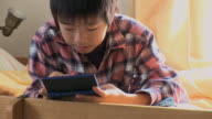 MS Boy (8-9) playing video game in kids room / Tokyo, Japan