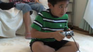 MS TU Boy (8-9) playing video game in living room / Tokyo, Japan