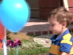 CU, ZO, MS, Boy (2-3) playing with balloons in front of house, Simi Valley, California, USA