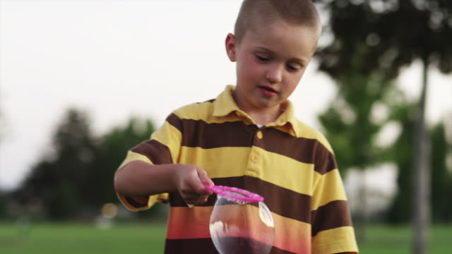 MS TU Boy (6-7) playing with bubble wand in park / Orem, Utah, USA