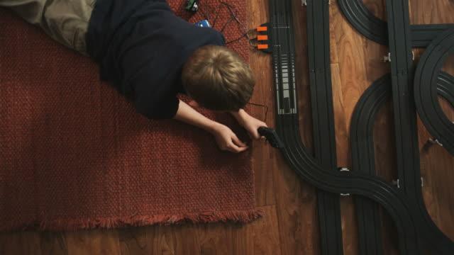 MS, Boy (10-11) playing with electric slot cars / Orem, Utah, USA.
