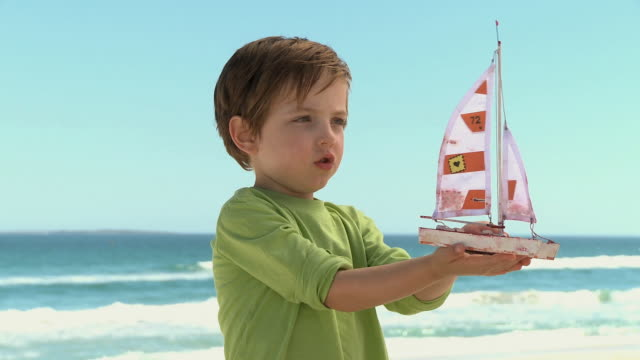 Lillle Boy Toys Boats : Ms boy playing with toy boat on beach cape town south