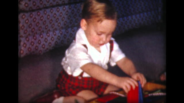 1957 boy plays with colored Christmas blocks