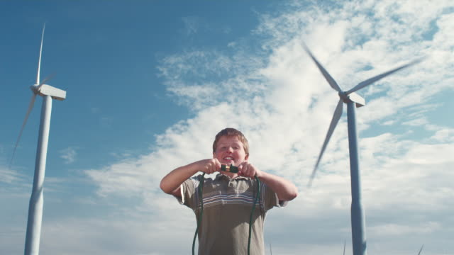 MS Boy plugging cords together in front of wind turbines / Zillah, Washington, USA