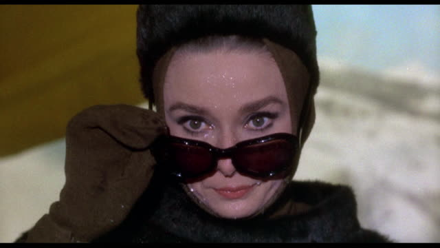 Boy points water gun at woman (Audrey Hepburn) before pulling trigger