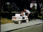 WS PAN Boy pushes another boy in soapbox go-cart along sidewalk / USA