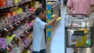 MS SELECTIVE FOCUS Boy (8-9) putting candy in shopping trolley and putting it back on shelf after father disagrees in supermarket, Richmond,  Virginia, USA