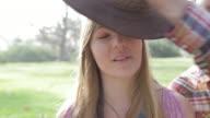 CU Boy putting large cowboy hat on girls head / Los Angeles, California, United States