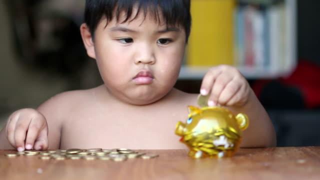Junge putting Geld im Sparschwein