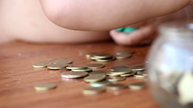Boy putting money in piggy bank