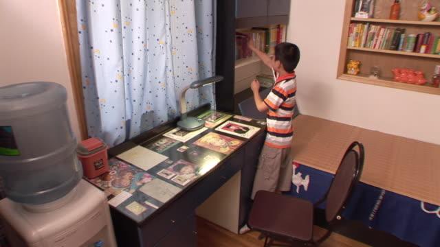 WS, HA, Boy (12-13) reading at desk, Shanghai, China