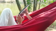 boy rest in hammock and using tablet