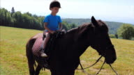 Boy riding horse at the meadow in mountains