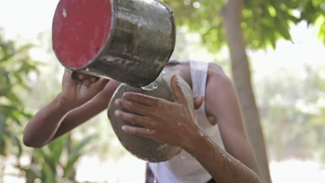 MS boy rincing his shaved head with water / Bagan, Mandalay Division, Myanmar