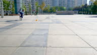 boy roller skating on marble square in beijing