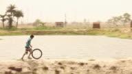 Boy rolling a tyre at riverside, Faridabad, Haryana, India