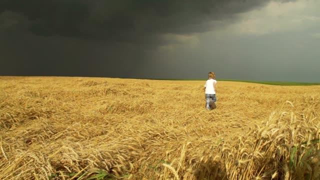 Boy running across a field of wheat