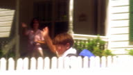OVEREXPOSED PAN boy running behind fence + waving to woman on porch in background / Florida