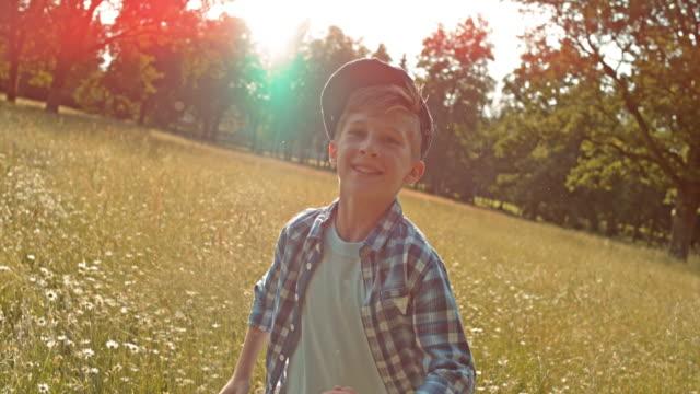 SLO MO TS Boy running in high grass in summer