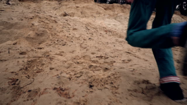 Boy running on a sandy cliff in slow motion