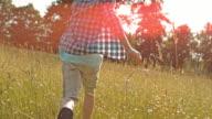 SLO MO TS Boy running through high grass in sunshine