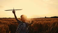 SLO MO Boy running with airplane in wheat field