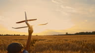 SLO MO Boy running with airplane toy through wheat field