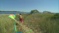 HA WS Boy running with kite along beach path with family following / Phippsburg, Maine, USA