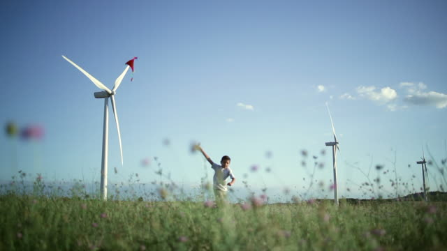 MS Boy running with kite in windfarm / Toulouse, Midi-Pyrenees, France