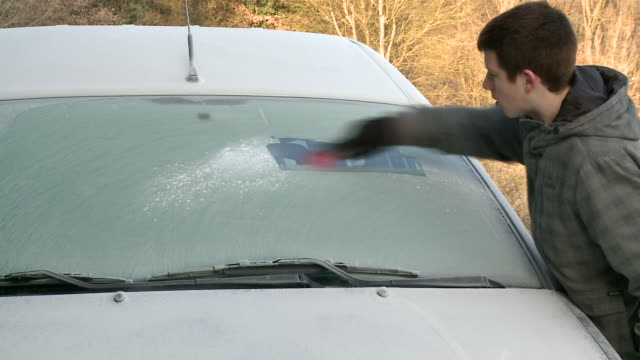 MS Boy scraping ice of car front glass / Kastel, Rhineland-Palatinate, Germany