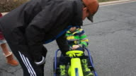 Boy sits in gocart and pedals however gocart does not function and father and sister try and help.