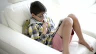 Boy sits on white sofa and completes crossword puzzle