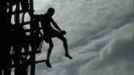 Boy sits on wooden tower during land diving ritual, Pentecost, Vanuatu