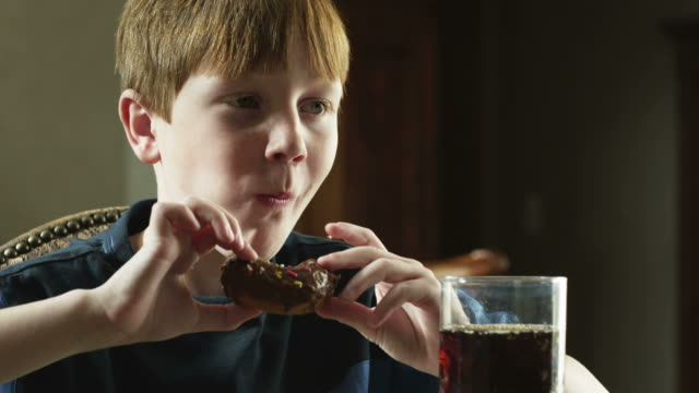 CU Boy (10-11) sitting at table, having cola and doughnut, American Fork, Utah, USA