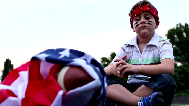 Boy sitting next to American football ball with us national flag