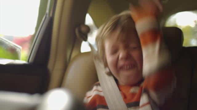 MS Boy (4-5) sitting on back seat of car and pulling funny faces / Atlanta, Georgia, USA