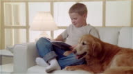 MS boy sitting on sofa with Golden Retriever and reading book