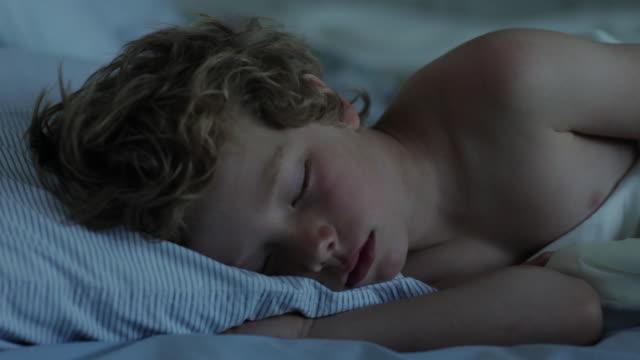 CU Boy sleeping on bed / WOLFEBRO, NH, USA