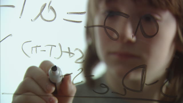 CU RACK FOCUS Boy solving math equation on glass with marker/ New York City
