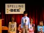 Boy spelling word at microphone in spelling bee / sitting down / Los Angeles, California