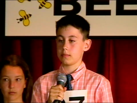 Boy spelling word on stage in spelling bee / celebrating after spelling word correctly / Los Angeles, California