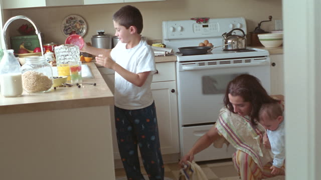 MS Boy spilling cereal bowl off counter and helping mother clean kitchen floor while she holds baby / Washington State, USA