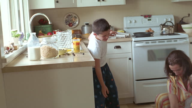 MS Boy spilling orange juice and helping mother clean cereal off kitchen floor while she holds baby / Washington State, USA