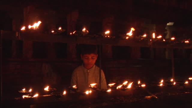 MS, Boy (8-9) standing behind lit oil lamps, Hampi, Karnataka, India